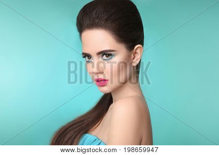 Closeup portrait beauty girl makeup. Matte lipstick. Beautiful fashion woman brunette with eye shadow and pink lips isolated over turquoise background.