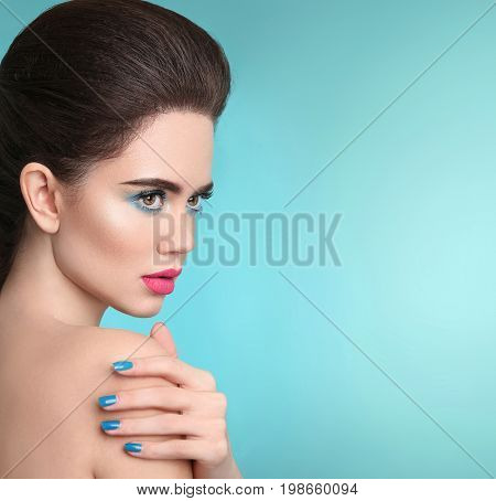 Beauty makeup. Matte lipstick. Closeup portrait girl with Manicured nails. Beautiful fashion woman brunette with eye shadow and pink lips isolated over turquoise background.