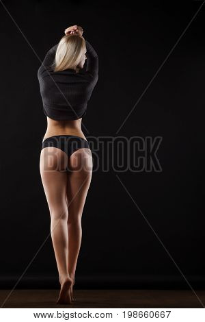 Muscular attractive fitness woman on gray background in studio. Trained female body