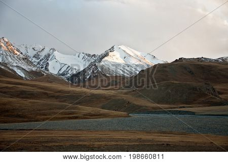 The rays of the evening sun on the tops of mountains in Tien Shan Kyrgyzstan