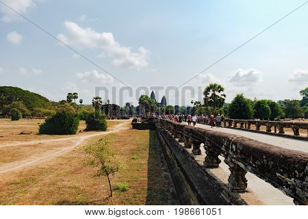Siem Reap, Cambodia - February 1, 2016: Unidentified tourists visit to Angkor Wat temple, Siem Reap, Cambodia. The main road to Angkor Wat which runs tours