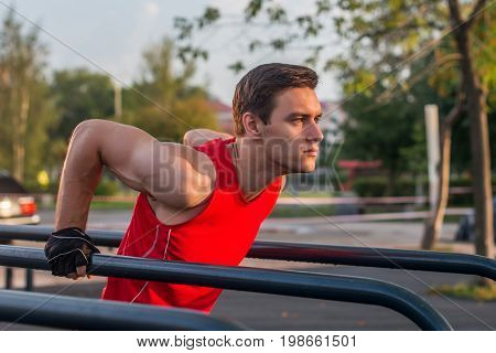 Fit man workout out arms on dips horizontal bars training triceps and biceps doing push ups outdoors