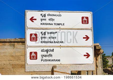 Hampi, India - November 20, 2012: Signpost for tourists with the pointer to the ancient ruins of Hampi - Balakrishna Temple, Krishna Bazaar and Pushkarani, Hampi, Karnataka, India.