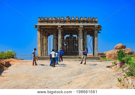 Hampi, India - November 19, 2012: Unidentified Indian tourists visit to the famous landmark. Hindu people walking inside of Ganesh statue in the ancient temple of Hampi, Karnataka, India. Side view