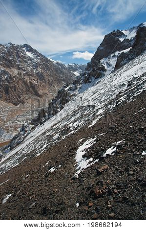Hunter goes on the trail on a steep rocky in the Tien Shan mountains. Kyrgyzstan.