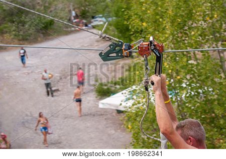Ukraine Migea - July 30 2017: Zipline. Equipment for safe sliding on steel cable. Male hands close-up while flying. Impact Trolley - roller for high-speed zipline.