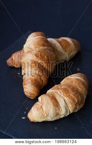 croissant buns on a black wood  background