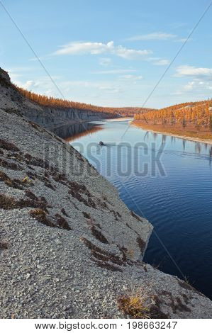 Boat with fishermen on the Siberian river in the fall. Riverbed Moiyerokhan in Evenkia in September during the rafting and fishing Krasnoyarsk region Russia