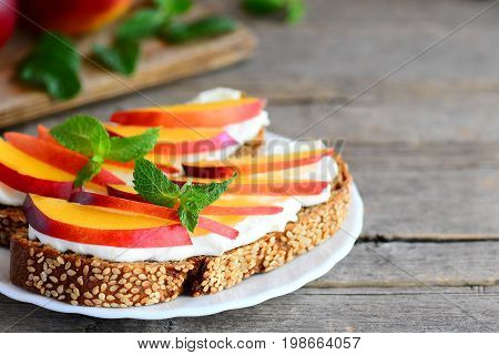 Nectarine and cream cheese toast sandwiches. Open sandwiches made of rye bread with cream cheese and fresh nectarine slices on a white plate and vintage wood background with copy space for text