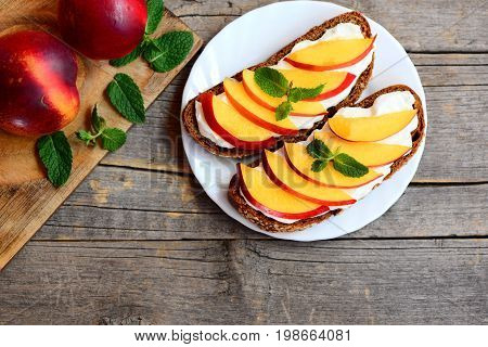 Summer nectarine and cream cheese sandwiches. Rye bread open sandwiches with cream cheese, fresh nectarine slices and mint on a white plate and vintage wooden table. Summer breakfast idea. Top view