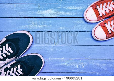 Two pairs of sporting sneakers blue men's sneakers and red women's on an old wooden background empty space in the middle