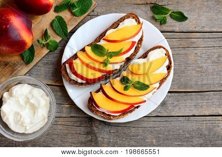 Easy nectarine and cream cheese sandwiches. Rye bread open sandwiches with cream cheese, ripe nectarine slices and mint on a white plate and old wooden table. Summer breakfast recipe. Top view