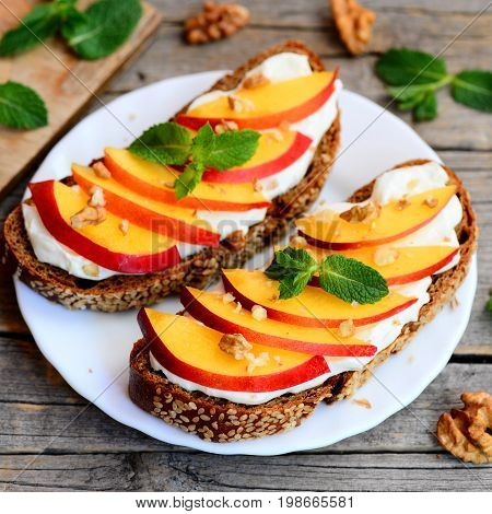 Sweet nectarine, walnuts and cream cheese sandwiches. Rye bread open sandwiches with cream cheese, ripe nectarine, walnuts and mint on a white plate and wooden table. Summer dessert recipe. Closeup