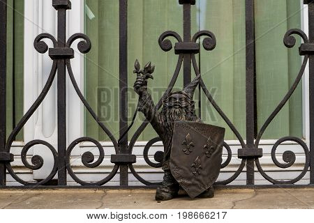 Wroclaw Silesia Poland - July 25 2017: Miniature bronze figure of a gnome with a shield on the window sill of a house in the city center.
