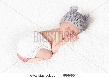 Newborn baby boy asleep and wearing a knitted hat.