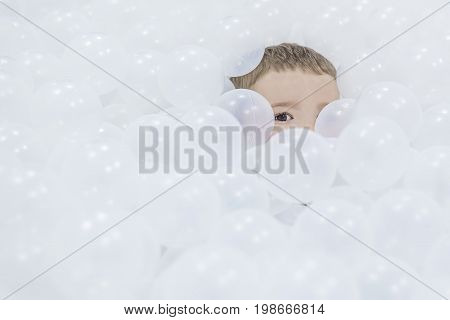 The boy hides in white plastic balls in the playroom. Only the head of the child and one eye are visible. Focus on the eyes of the child.