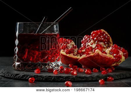 A red berry cocktail with black straws and a part of a pomegranate on a black background. Alcoholic antioxidant beverage. A grain of bittersweet garnet.  Expensive delicacy drinks for gourmets.