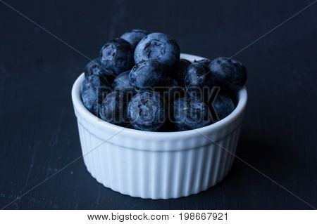 Blueberries in a bowl on a black background