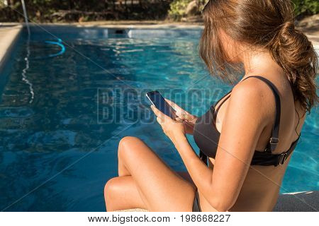 Back view of woman using smartphone sitting on poolside in sunny day.