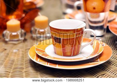 spottily orange tea cup and candles, service