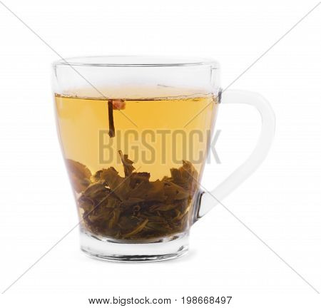 A close-up of a glass tea cup full of green tea isolated on a white background. A cup with hot liquid and green tea leaves. Winter organic beverage. Tasty healthy tea. Chinese drink.