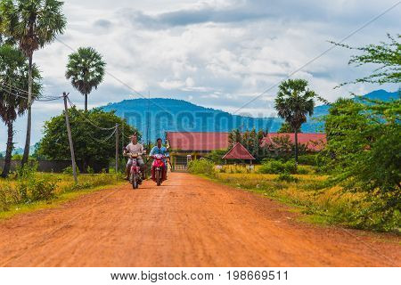 Kampot, Cambodia - December 14, 2016: Cambodia rural scenery with two men who hold fishing rods drive scooters on a red dirt road with palmyra palm trees (palm fruit) seen.