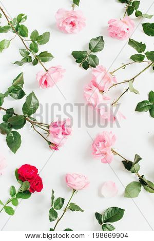 Floral pattern made of pink and red roses green leaves branches on white background. Flat lay top view. Valentine's background. Floral pattern. Pattern of flowers. Flowers pattern texture