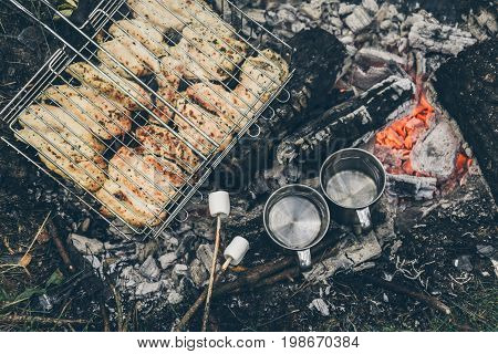 top view on bonfire with chicken meat and cup with water and murshmallows
