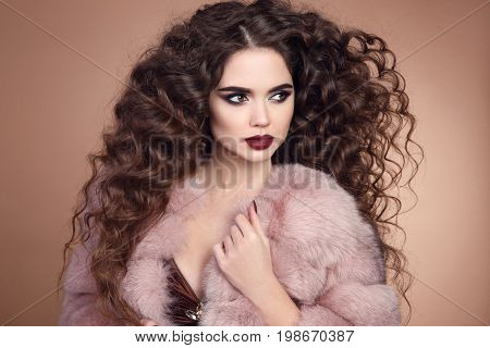 Beauty hair. Fashion portrait of beautiful brunette woman model with marsala matte lips makeup and long curly hairstyle in luxury fur coat isolated on beige background