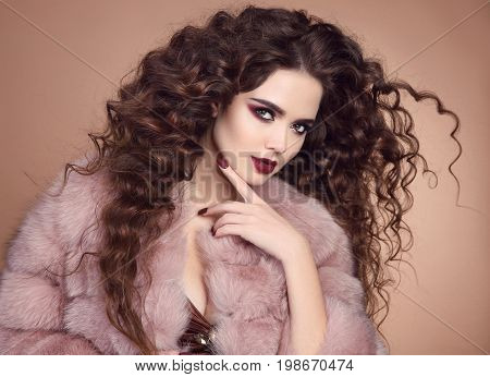 Beauty hair. Glamour fashionable portrait of beautiful brunette woman model with marsala matte lips and long curly hairstyle in luxury fur coat isolated on beige background