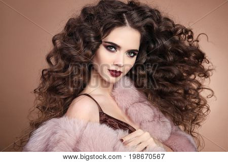 Hairstyle. Curly hair. Fashion brunette girl with long curly hair. Beauty makeup. Glamour portrait of beautiful brunette with marsala matte lips in pink fur coat isolated on beige background.