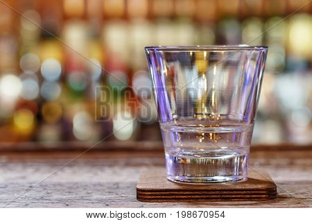 An empty glass for whiskey on the bar in the restaurant or in the pub. Background for writing text design