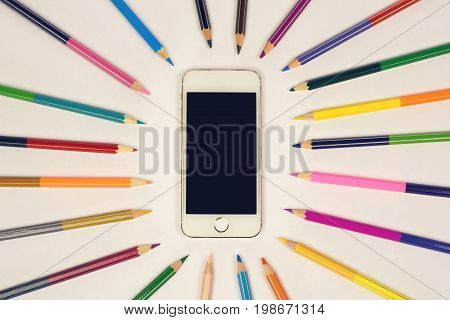 white smart phone on a light background colored pencils around. Top view on office desk. mock up sample
