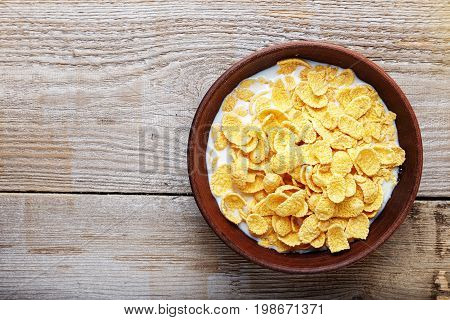 Cornflakes in a brown clay plate on a shabby wooden background space for text