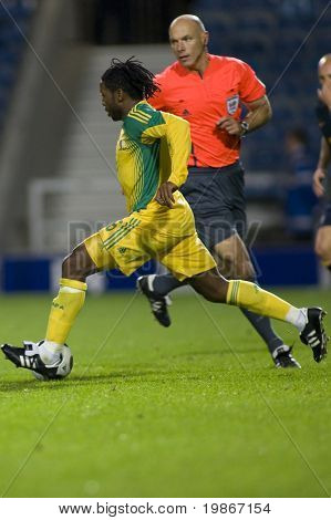 LONDON, UK AUGUST 19 Macbeth Sibya sprinting with the ball, past the referee Harry Webb playing in the international football match between Australia and South Africa held at Loftus Road London
