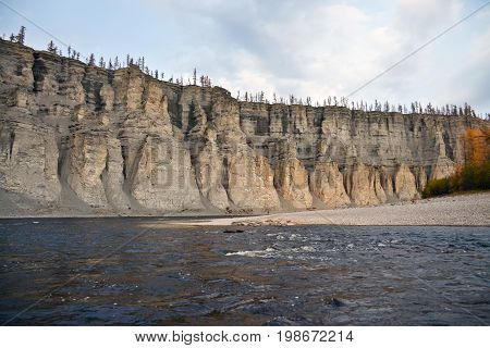 Rocky coast of the Siberian rivers in the fall. Riverbed Moiyerokhan in Evenkia in September during the rafting and fishing Krasnoyarsk region Russia