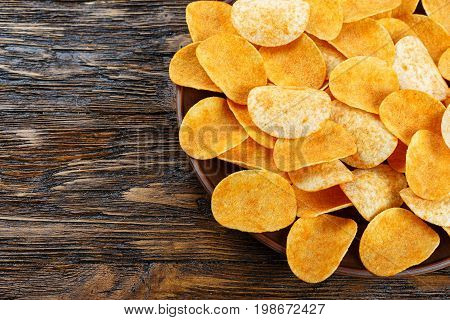 Crispy potato chips in an earthenware dish on old kitchen table. top view
