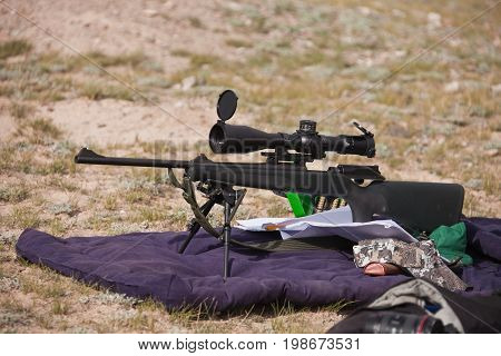A hunting rifle with optical sight and bipod support while zeroing on the hunt in the mountains of Tien Shan Kyrgyzstan