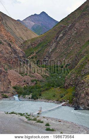 Pedestrian bridge across the river in the mountains of Tien Shan. Hanging bridge over a mountain river in Kyrgyzstan