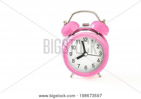 Retro pink alarm clock with 2 minutes to 8 o'clock on it. Isolated on white background. Close up