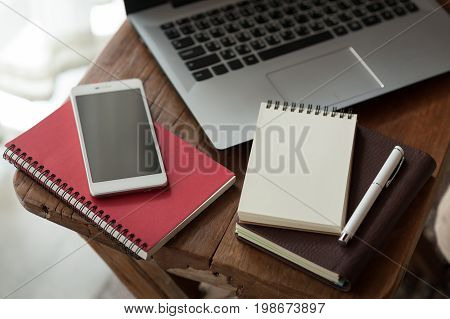 Pen notebooks smartphone and laptop computer on small wood table. Working at home on weekend concept