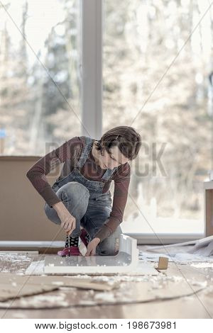 Retro style image of a woman assembling a DIY furniture at home kneeling on the floor in front of a bright glass window working with a screwdriver.