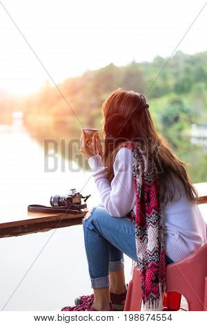 Young woman's hand holding cup of tea on a cold and morning day. Travel Concept