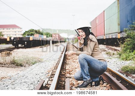 Engineer asia woman checking railways and call radio for civil and construction. Engineer Concept.