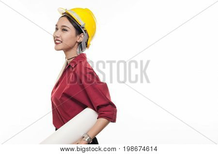 Young Asian woman architect with red shirt and yellow safety helmet smiling while carrying blueprint papers. Industrial occupation people concept