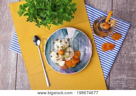 Cold and tasty vanilla ice cream with physalis, pumpkin seeds, and dried apricots on a yellow fabric and on a wooden background. A little tea spoon near the dessert. A beverage on a striped cloth.