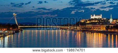 Night view on new bridge in Bratislava with castle on right side and lights reflection on Dunaj river.