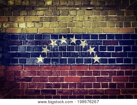 Faded Venezuelan flag on an old brick wall background with a dark vignette