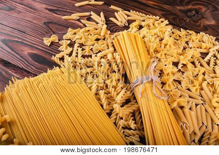 Top view of beautiful variety of pasta on a wooden background. Different kinds of perfectly organized macaroni on a brown table. Delicious farfalle, fettuccine, noodles, fusilli and penne rigate.
