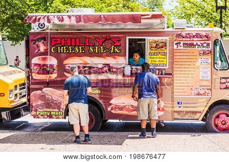 Washington DC USA - July 3 2017: Food trucks on street by National Mall with Philly's Cheese steak storefront on Independence Avenue